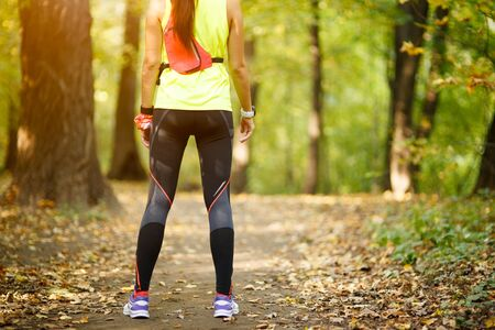 female athlete: young fit woman doing exercise in park, rear view