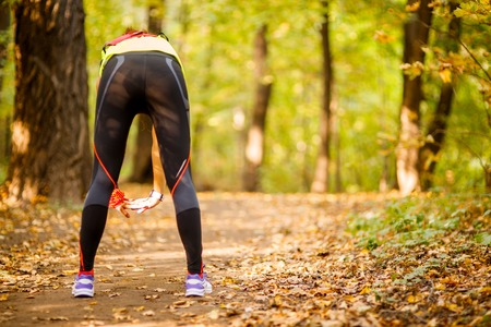 gym clothes: young fit woman doing exercise in park, rear view