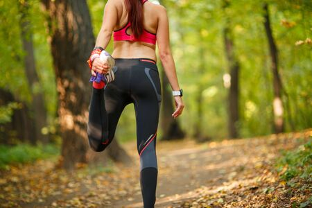 Detail of man stretching legs before jogging in autumn nature