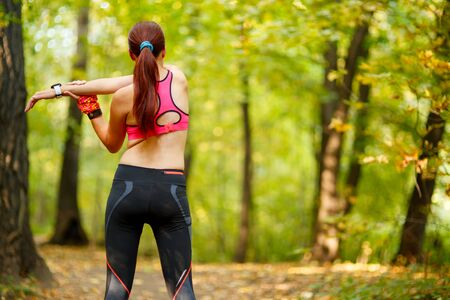 spandex: attractive woman runner stretching before her workout in park