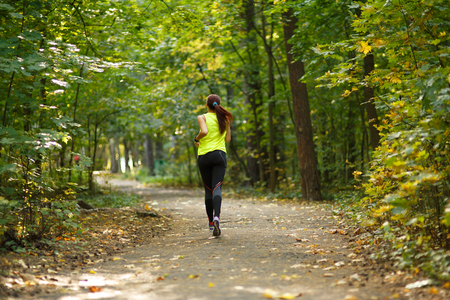 jungle: young fitness woman running at forest trail