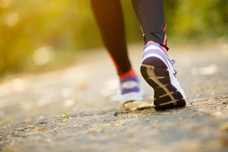 piernas hombre: Pies del corredor que se ejecutan en la carretera de primer plano en los zapatos en el parque