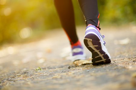 people in action: Runner feet running on road closeup on shoes in park Stock Photo