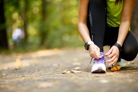 girl in the forest: young woman runner tying shoelaces in park