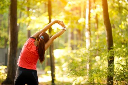 estiramiento: Mujer ejercicio en el parque, que se extiende hasta las manos Foto de archivo