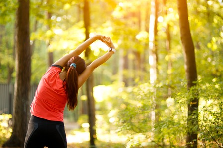stretching exercise: woman exercising in park, stretching hands up