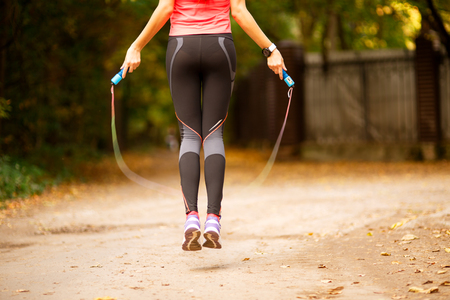 woman rope: Close up of woman feet jumping, using skipping rope in park Stock Photo