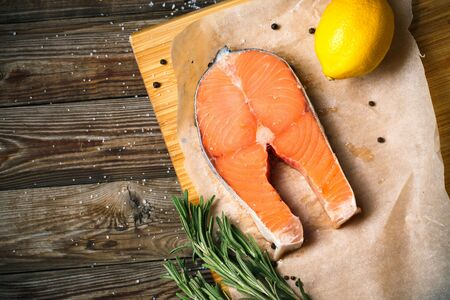 Top view image of fresh salmon fillet with herbs, spices and lemon slices on wooden background