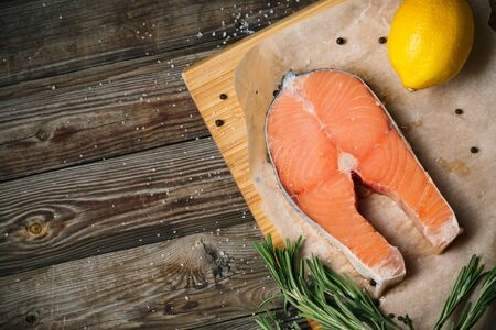 king salmon: Top view image of fresh salmon fillet with herbs, spices and lemon slices on wooden background