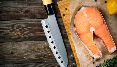 color: Fresh and raw steak salmon on wooden cutting board with rosemary and pepper