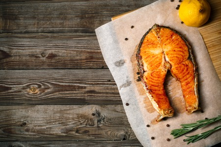 Grilled salmon on wooden table, top view with copyspace