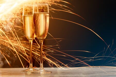 white party: champagne glasses with fire on black background. Blue and gold flare at background Stock Photo
