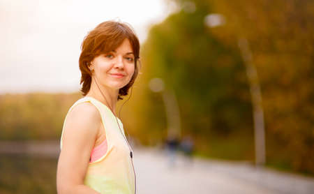 mp3: Young woman with mp3 player doing fitness in city park