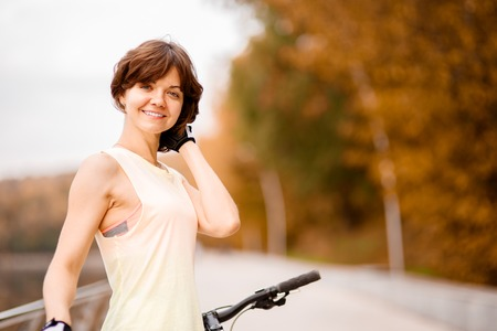 space weather tire: portrait of beautiful young woman with her bike outdoor