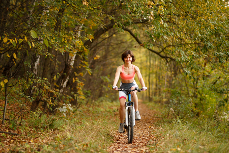 cruiser bike: woman riding bike on path in park full of trees toned