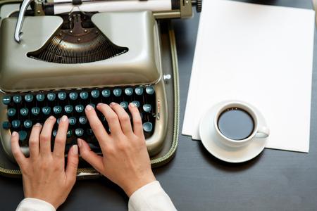 the typewriter: Primer del caf� y las manos que escriben en la vieja m�quina de escribir Foto de archivo