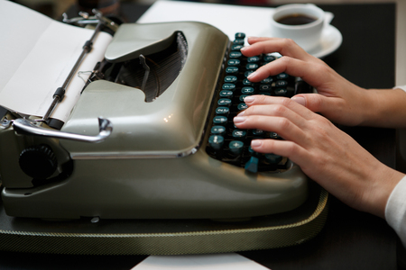 shoulder buttons: closeup of woman typing with old typewriter side view