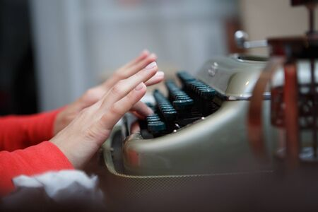 detective agency: closeup of the hands of a man typing on an old typewriter
