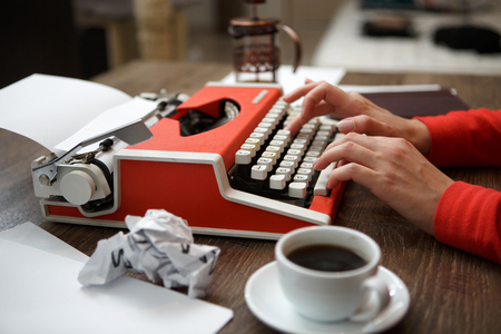 typewriter key: Side view of red typewriter, cup of coffe, crumpled paper Stock Photo