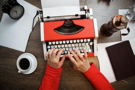 木製の机の上に白紙の用紙とビンテージ赤タイプライター