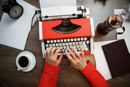 Vintage red typewriter with blank paper on wooden desk Standard-Bild