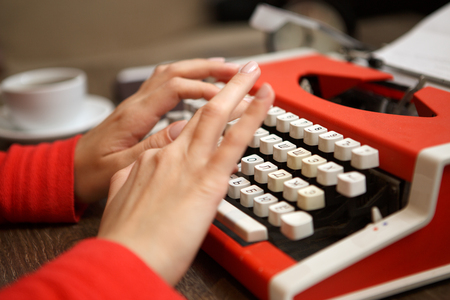 screenwriter: human hands writing on old red typewriter Stock Photo