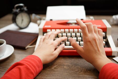 screenwriter: Vintage red typewriter with blank paper on wooden desk Stock Photo