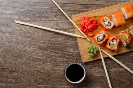 copule: Sushi maki set with copule chopsticks on wooden preparation table at table