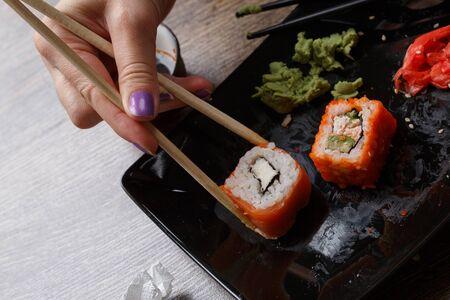 philadelphia roll: Sushi. Hand with chopsticks takes philadelphia roll