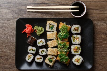 exotically: Various of sushi rolls with chopsticks on wooden table Stock Photo