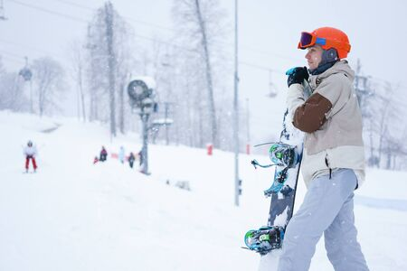 symbol sport: M�nner Snowboarder tragen orange Helm, graue Jacke, schwarz und blau glovesaann graue Hose mit Snowboard und Blick auf die sch�ne Berglandschaft