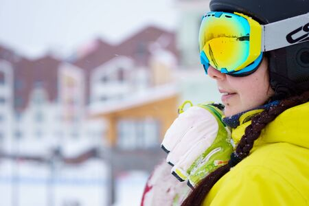 yellow jacket: Female snowboarder wearing black helmet, yellow jacket, white and green gloves standing with snowboard