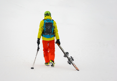 weary: Sad and weary skier with backpack goes away, dragging skis.