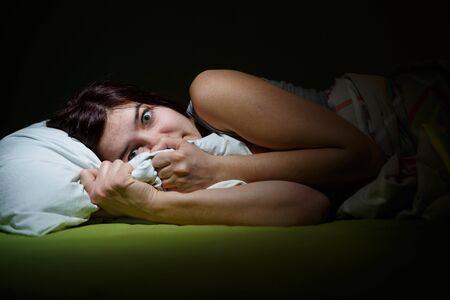 Mujer joven en la cama con los ojos abiertos que sufren insomnio. Dormir concepto y temas de pesadilla