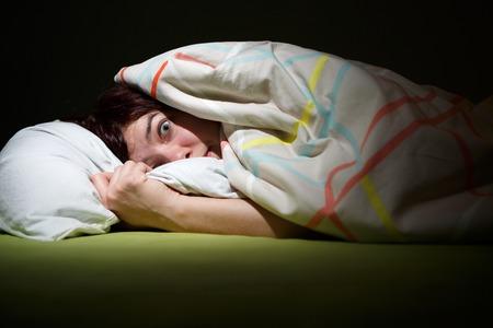 Jeune femme au lit avec les yeux ouvert souffrant d'insomnie. Sleeping questions conceptuelles et cauchemar