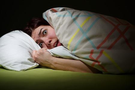 Mujer joven en la cama con los ojos abiertos que sufren insomnio. Dormir concepto y temas de pesadilla Foto de archivo