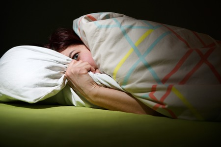 Young woman in bed with eyes opened suffering insomnia. Sleeping concept and nightmare issues Imagens