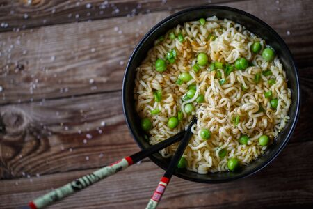 noodles: Top view of chinese noodles with fresh peas and chopped green onion on wooden table. Stock Photo