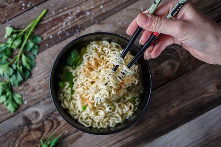 santa cena: Vista superior de las manos con los palillos la celebraci�n de los tallarines chinos con guisantes frescos y cebolla verde picada en mesa de madera.