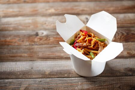 chinese noodles: Noodles with pork and vegetables in take-out box on wooden table