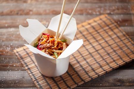 Noedels met varkensvlees en groenten in take-out box op houten tafel