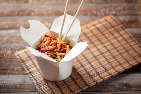 noodles: Noodles with pork and vegetables in take-out box on wooden table