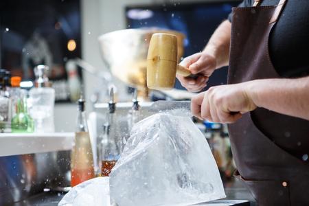 ice crushed: Barman mannually gemalen ijs met houten hamer en metalen mes.