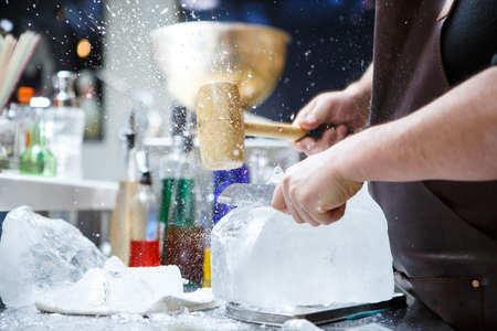 bartender: Bartender mannually crushed ice with wooden hammer and metal knife.