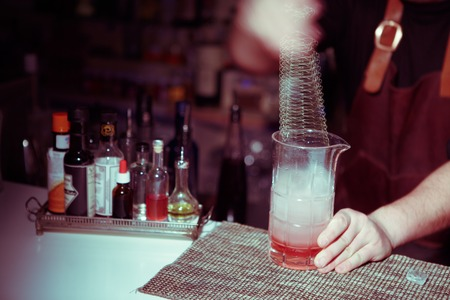 distilled alcohol: Bartender nixed cocktail in glass cup. Image toned with blue-yellow tones.