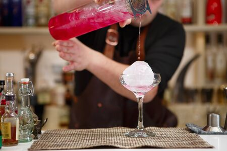distilled alcohol: barman pouring a pink cocktail drink Stock Photo