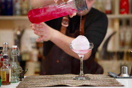 barman: barman pouring a pink cocktail drink Stock Photo