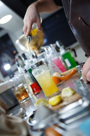 straining: Bartender is straining cocktail in a glass