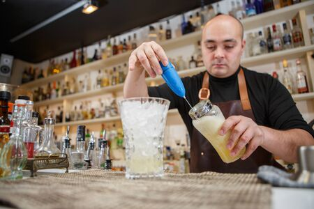 behind: barman using a hand mixer to prepare drink in  bar or pub