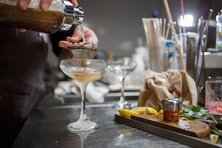 fruit bars: Bartender coocks cocktail behind a bar counter Stock Photo